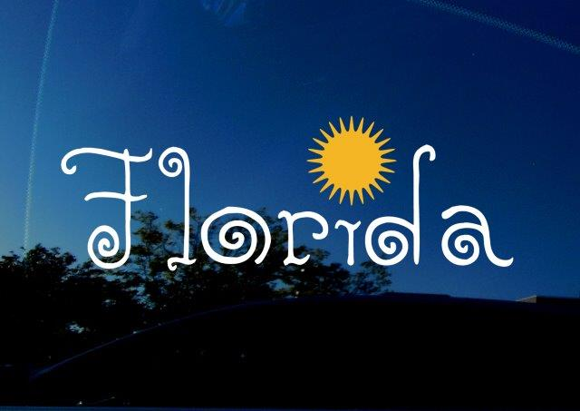 """Florida (FL) state decal for cars, trucks, SUVs, laptops, and more. Sticker featuring curly letters, and sun as the dot on the 'i"""". White vinyl on reflective car background."""